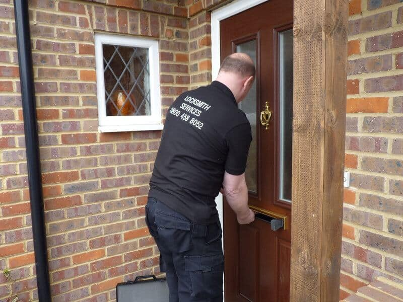 Locksmith working on unlocking a locked door