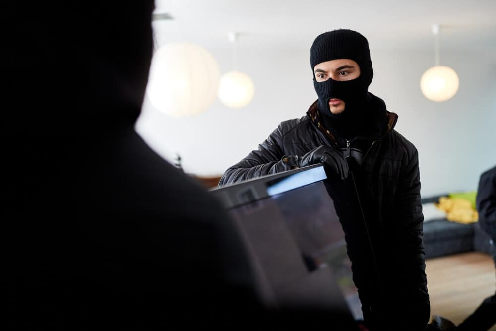 Burglars Stealing A TV From A Home