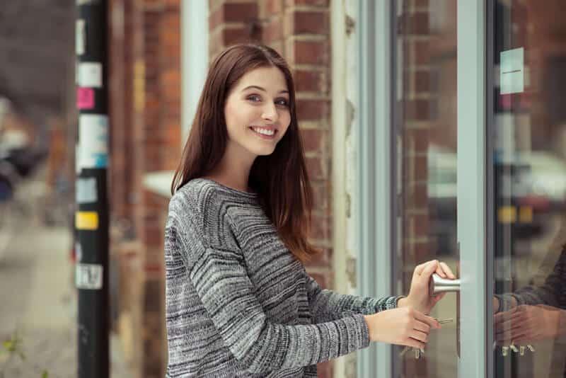 Woman Smiling Opening A Door